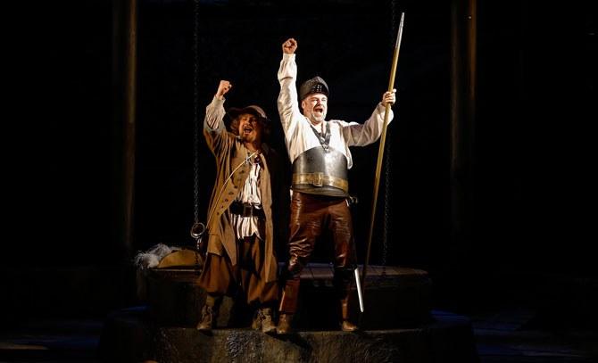 """Cervantes (Jochen Schmeckenbecher) und sein Diener Sancho Pansa (Glenn Desmendt) spielen den Mitgefangenen die Geschichte von Don Quichotte, dem """"Ritter von der traurigen Gestalt"""" vor.   © Christian Husar"""